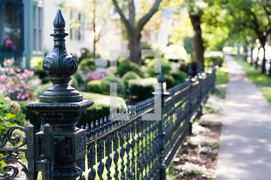 Wrought iron fence along a sidewalk.