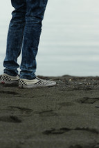 feet in sneakers standing on black sand