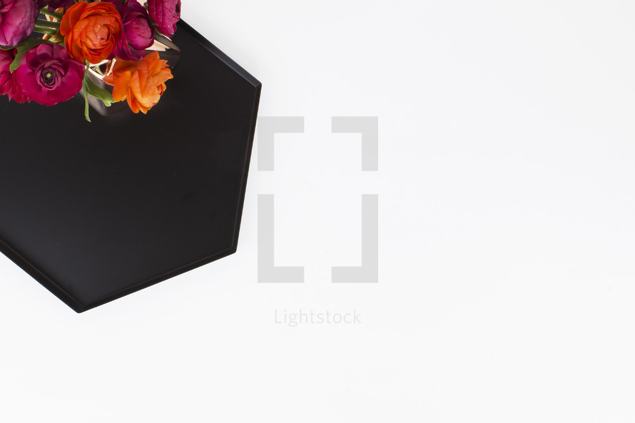 flowers on a black tray on white background
