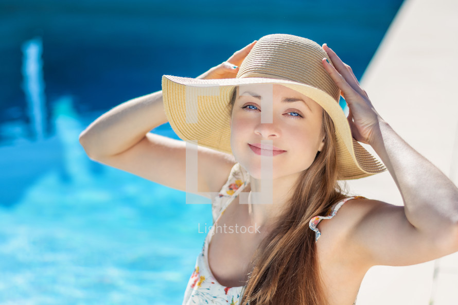 young woman in sunhat sitting by a pool