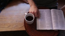 man reading a Bible with a cup of coffee