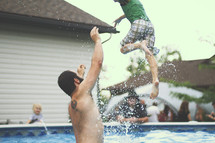 a man tossing a boy child in a pool