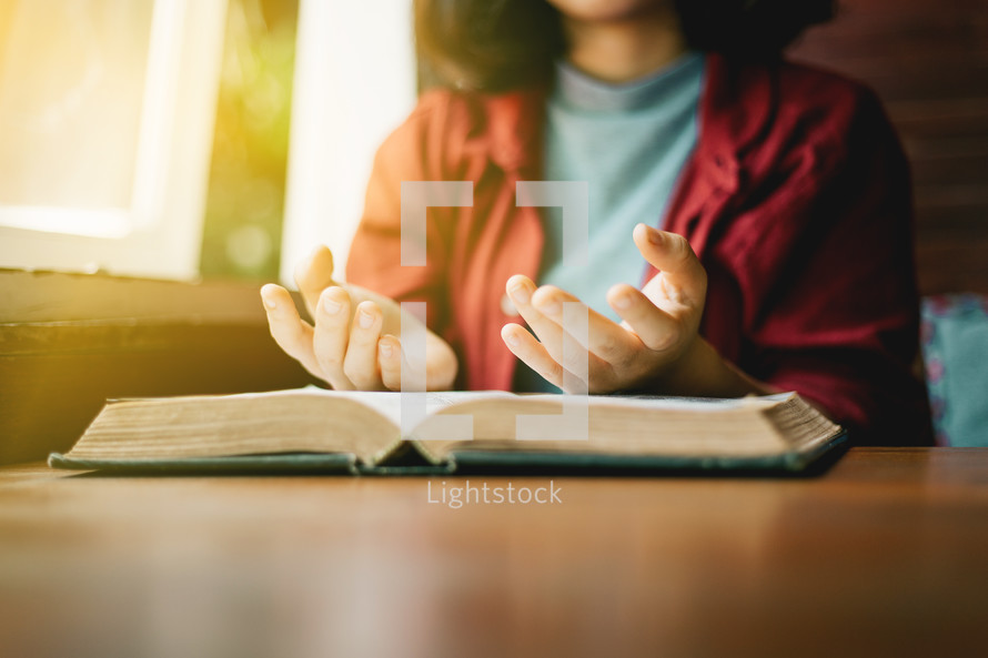 a woman sitting at a table praying over an open Bible
