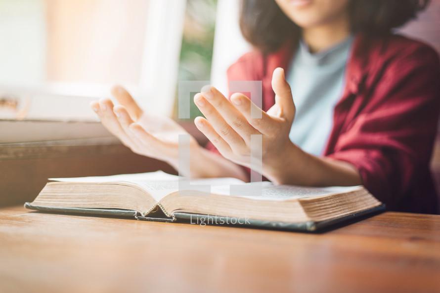 a woman praying over an open Bible
