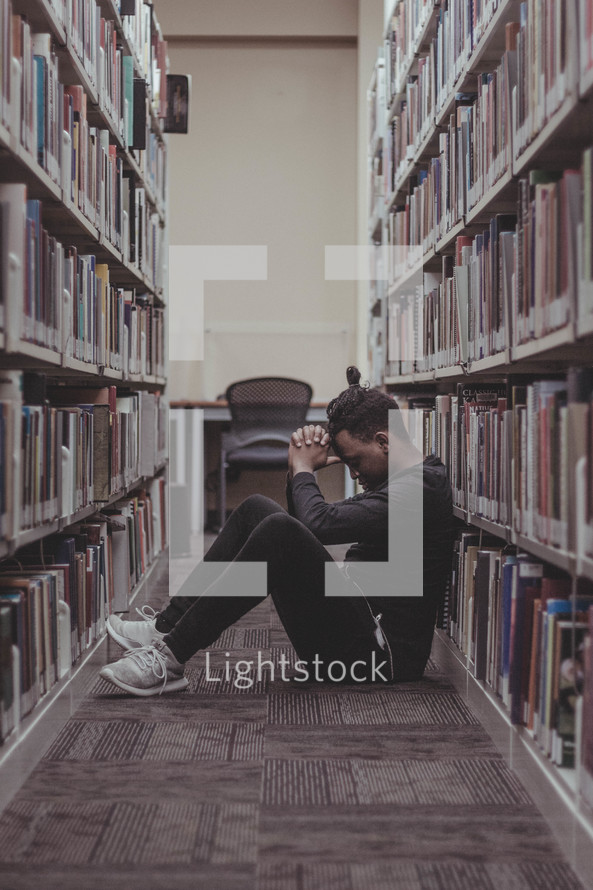 a man praying in a Library