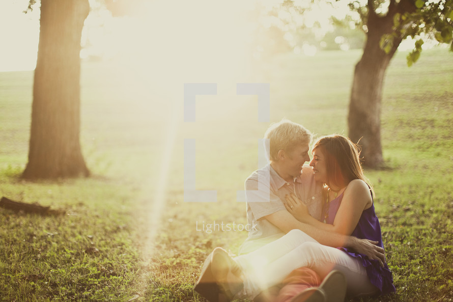 couple in an embrace sitting on the grass