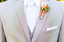 Chest of man in gray suit with orange boutonnière.