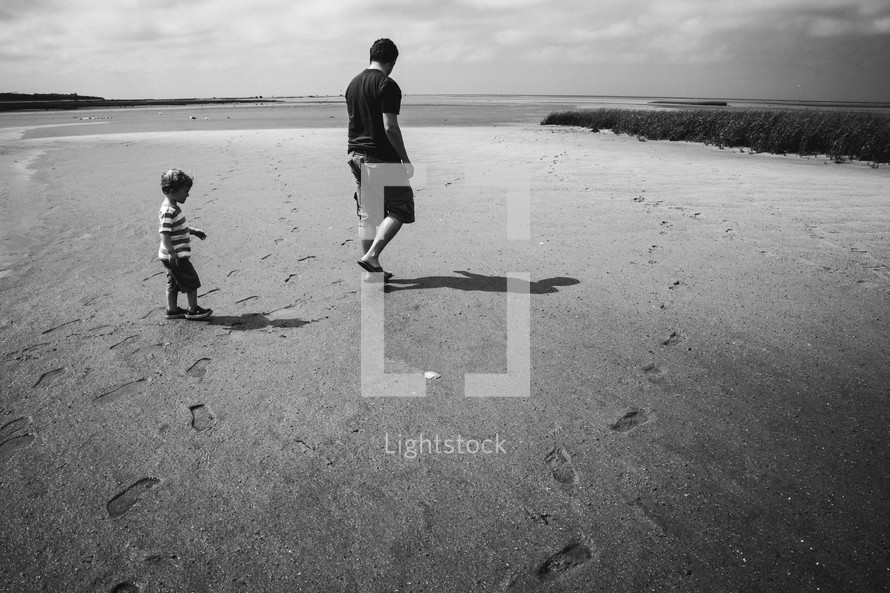 father and son walking down a beach