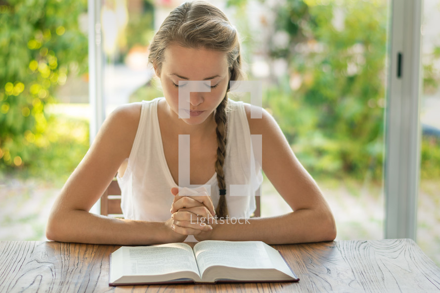 a woman reading a Bible and praying in the morning
