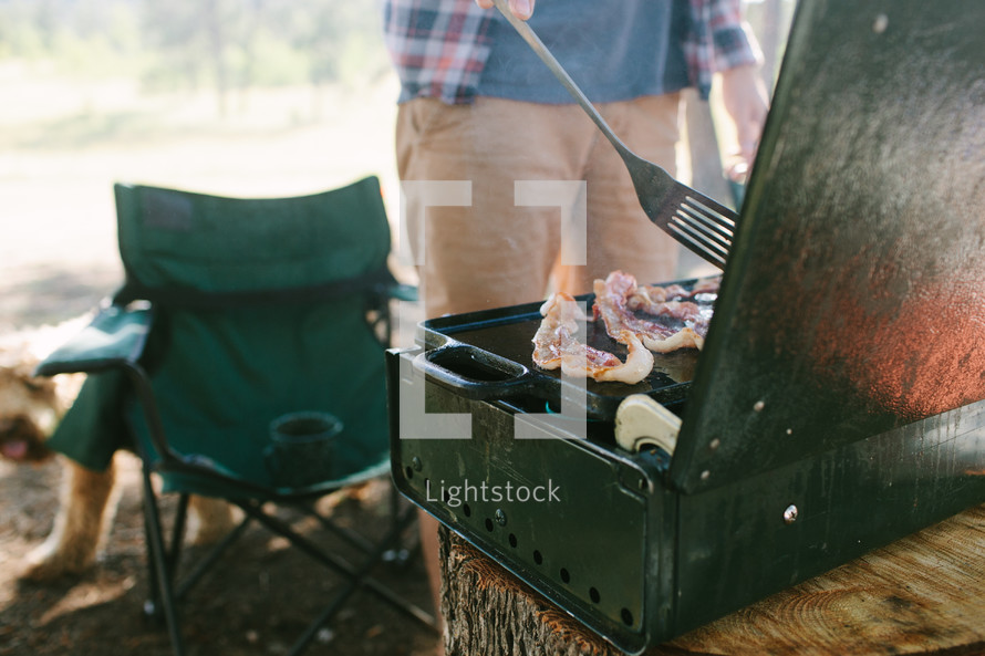 a man flipping bacon on a campsite