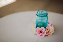 flowers around a blue mason jar