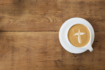 Cross shape in a latte drink on a wooden table.