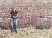 man reading a Bible against a brick wall