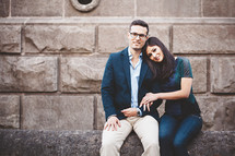 a couple sitting on a stone wall