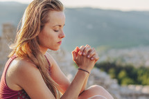 a young woman praying outdoors