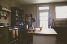 a woman writing a letter in her kitchen