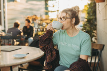 a woman at a coffee shop drinking coffee