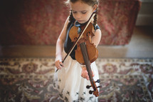a girl child practicing her violin