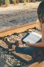 A young girl sitting on railroad tracks reading her bible.