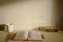 open Bible, coffee mug, journal, pen, and basket on a desk