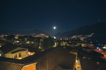 view over a city at night and the glow of the full moon