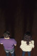 Couple standing in the aisle in a dark, empty church.