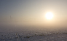 sunrise over field covered with snow