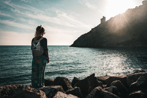 a girl with a backpack standing on a shore at sunrise