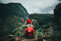 a woman resting while backpacking through a forest