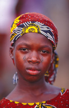 a girl child in traditional clothing with tribal face markings