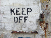 """Keep Off"" sign on a wall."