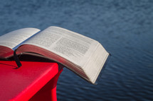 Bible on a Muskoka chair with a lake in the background.