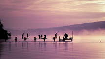 silhouettes of people on a dock under a pink sky at sunset