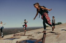 women balancing on pipes on a mountaintop