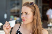 a young woman drinking espresso in a city