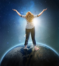 woman standing on top of the world with her arms raised in worship to God