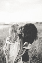 a girl kissing her mother on the cheek