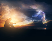 silhouette of a man praying during a storm