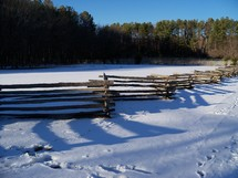 A wooden fence cascades across the landscape covered by fresh snow on a winter day in Virginia.