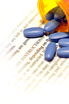 Bright blue medicine tablets spilling from a prescription container lying on after-care instructions.