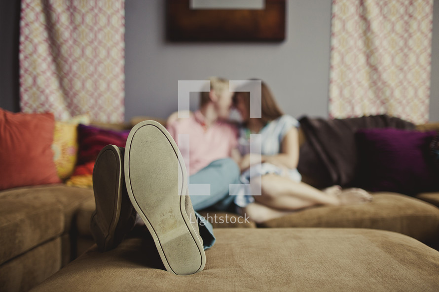 Couple sitting on couch looking at each other