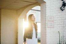 young woman standing in sunlight