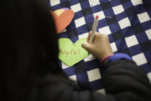 a child writing a word on a paper heart