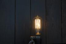 Edison bulb against blue wood background