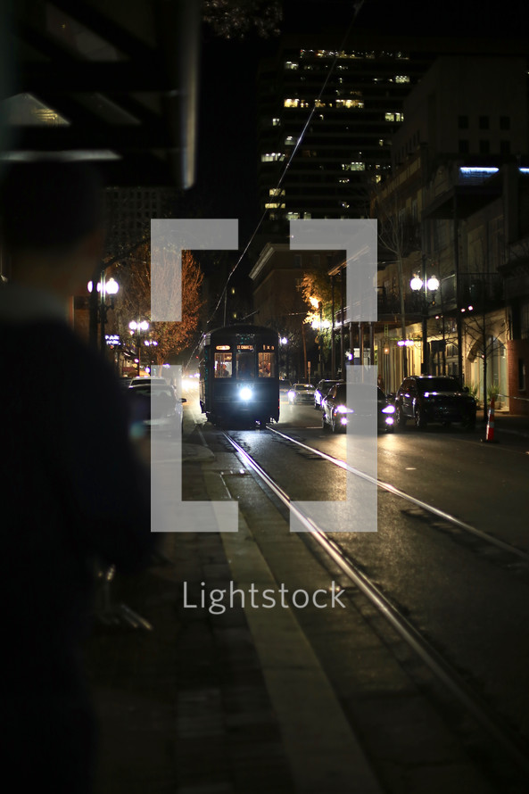 A streetcar on rail lines in New Orleans at night.