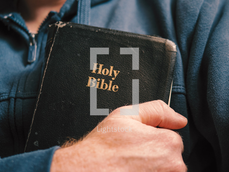a man holding a Bible to his heart