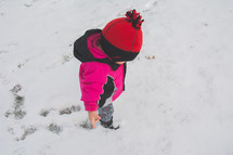 A toddler walking in snow