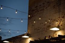 hanging lightbulbs over a courtyard