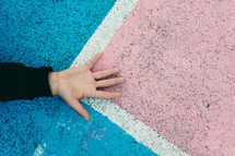 hand on colored pavement