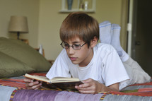 boy child reading on his bed